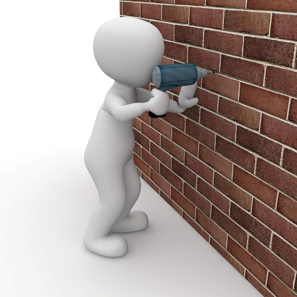 un omino intento a fare un buco nel muro, metafora di copy persuasivo